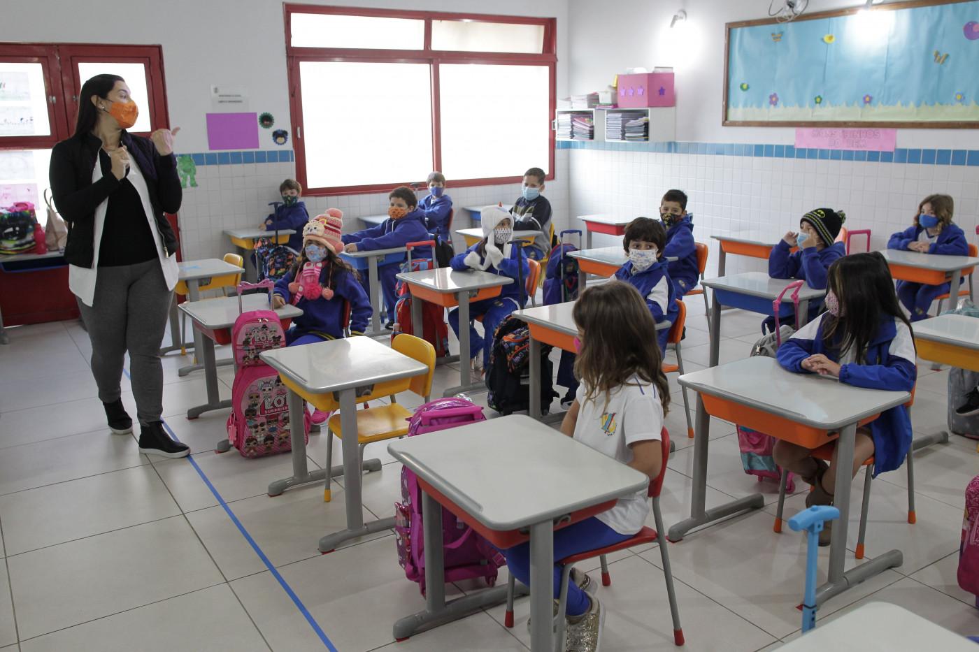 Professora dá aula presencial para crianças