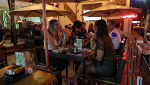 Três mulheres aparecem sentadas na mesa de um bar