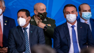 Sentados na bancada da frente durante posso de Ciro Nogueira, Hamilton Mourão, à esquerda, e Jair Bolsonaro, ambos de máscara e trajes sociais, sentam lado a lado, mas não se olham