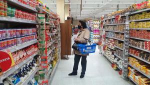 Mulher segura cesta em supermercado enquanto olha para prateleira
