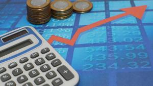 Imagem com uma calculadora, uma seta para cima e moedas representa o aumento da inflação