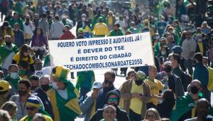 """Centenas de pessoas, a maioria usando camisa amarela, protesta em favor de Jair Boslonaro; uma faixa pede voto impresso e diz que está """"fechado com Bolsonaro até 2050"""""""