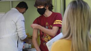 Adolescente arregaçando as mangas da blusa para receber a vacina contra a Covid-19