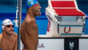 Gabriel, nadador paralímpico, com a língua para fora, touca de natação azul e óculos de natação vermelhos