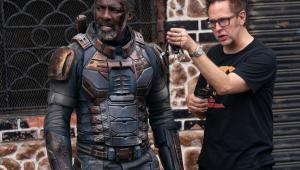 O diretor James Gunn, de camiseta preta e bermuda, orienta o ator Idris Elba, trajado como o vilão Bloodsport