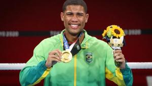 Com o uniforme do Time Brasil, Hebert Conceição dá largo sorriso,exibe a medalha de ouro com a mão direita e segura o mascote olímpico e um ramo de flores com a esquerda