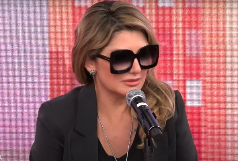 Antonia Fontenelle usa óculos escuros pretos e fala ao microfone no estúdio do programa Pânico
