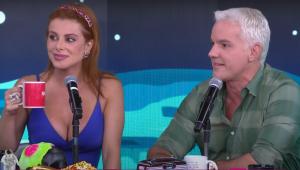 Deborah e Bruno estão sentados um ao ldo do outro, enquanto falam ao microfone no estúdio do programa Pânico. Deborah é ruiva e usa vestido azul decotado, Bruno é grisalho e veste camisa xadrez