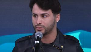 Agustin Fernandez usa jaqueta de couro e fala ao microfone no estúdio do programa Pânico