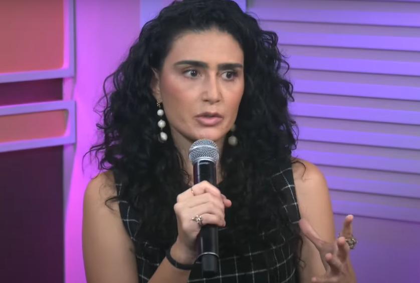 Cristiane gesticula e fala ao microfone no estúdio do Morning Show