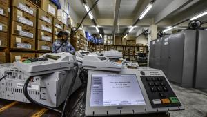 Duas urnas eletrônicas em evidência dentro de um espaço com várias caixas e outras urnas atrás