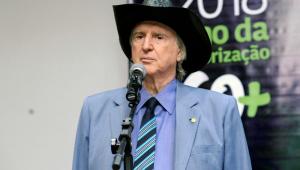 Sérgio Reis de terno azul e chapéu preto em frente a um microfone