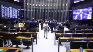 Imagem do plenário da Câmara vista do fundo, com muitos deputados de costa, um no telão e um saindo