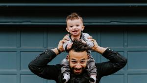 Pai com criança nos ombros, ambos estão sorrindo e ele segura os braços do bebê