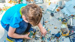 Criança brincando com vários pedaços de um objeto tecnológico espalhados pelo chão