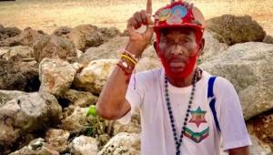 Homem idoso sentado em pedras em uma praia com um boné vermelho, barba pintada de vermelho, camiseta branca e pulseiras e colares coloridos. Ele está com o braço e o dedo indicador direitos para cima.