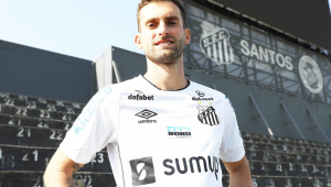 Léo Baptistão posa para foto com a camisa do Santos, com a arquibancada atrás