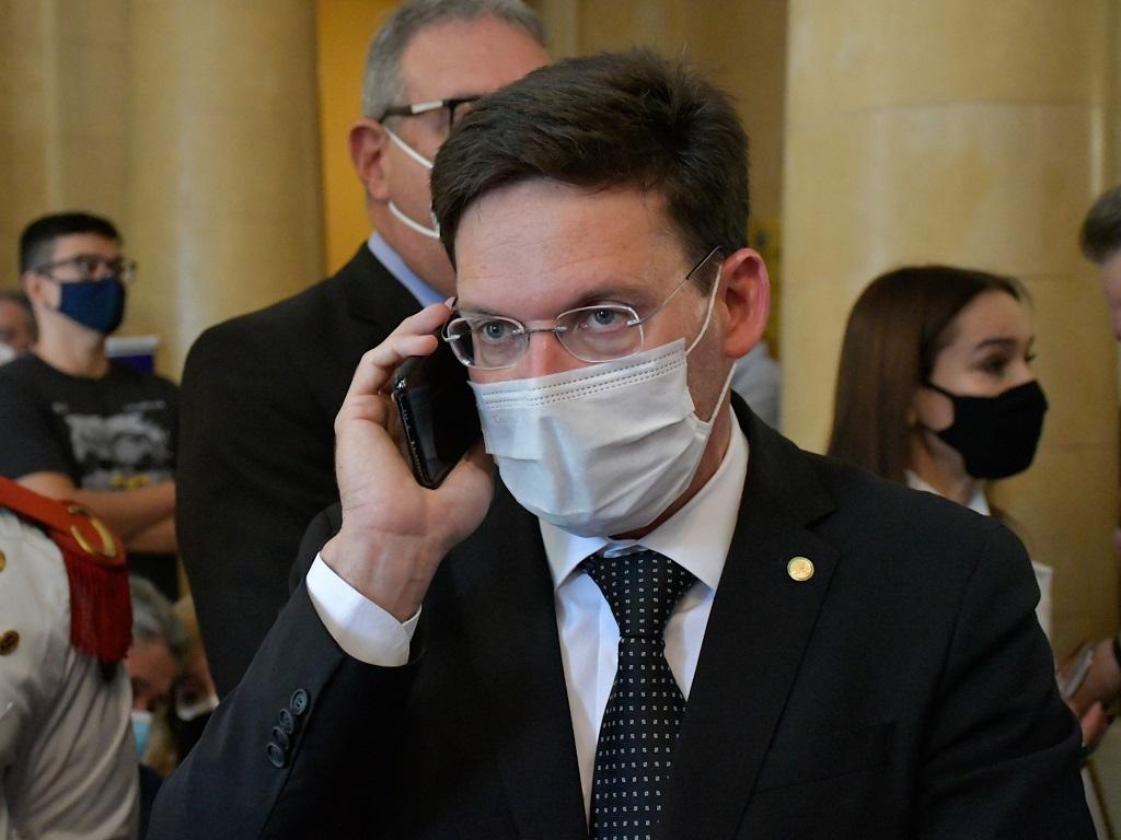 Ministro João Roma falando ao celular e usando máscara de proteção individual. Tem cabelos curtos castanhos e usa terno e óculos de grau