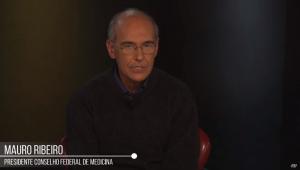 Mauro Ribeiro, homem careca e de óculos, usa suéter preto e está sentado olhando para a câmera