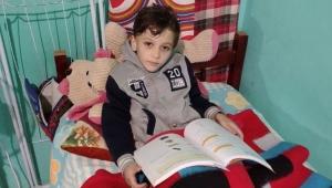 menino miguel sentado lendo um livro