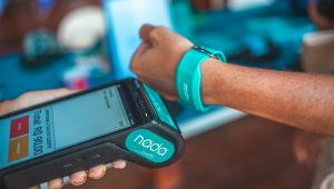 Braço esquerdo de uma pessoa usando uma pulseirinha de pagamento eletrônico chega perto da maquinha, segura pela mão de outra pessoa, para fazer o pagamento por aproximação