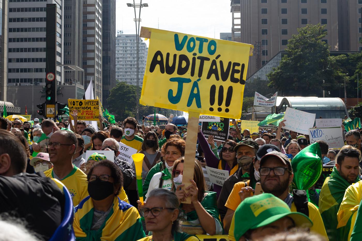 """Pessoas em manifestação pró-governo na Paulista segunrando um cartaz escrito """"voto auditável já'"""