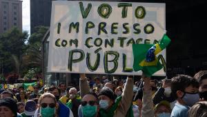 """Apoiadores de Jair Bolsonaro, a maioria usando roupa verde-amarela e máscara, amontoa-se perto do Masp; um grande cartaz com a mensagem """"Voto impresso com contagem pública"""" está aberto"""