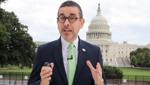 De paletó azul, camisa branca, gravata dourada e óculos de armação grossa, o jornalista Fernando Hessel (homem branco de 45 anos) gesticula com a Casa Branca ao fundo