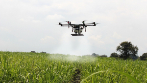 Espécie de drone jogando água sobre uma plantação verde