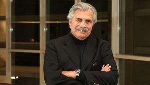 De braços cruzados, usando camisa e blazer preto, o ator Tarcísio Meira posa para um foto em sua casa