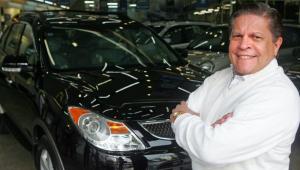 Empresário Carlos Alberto Oliveira homem de braços cruzados ao lado de carro