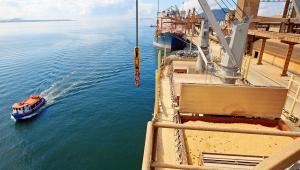 Porto de Paranaguá, um barco andando no mar e uma estrutura de metal ao lado