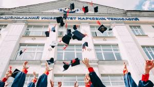 Universitários jogam chapéus para o alto (só os braços são vistos)