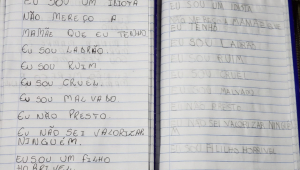 caderno com frases autodepreciativas escritas por menino
