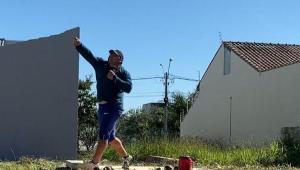 Atleta arremessa peso em um espaço aberto com grama, e céu azul ao fundo