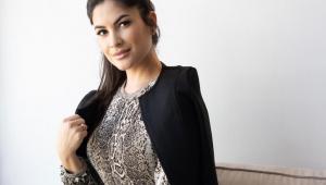 Mulher com o cabelo preso em um rabo de cavalo olhando para a câmera com a mão segurando em um blazer preto que ela está vestindo e por baixo uma camisa estampada de leopardo