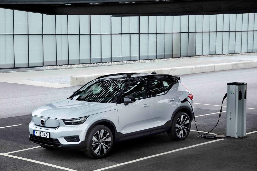 Carro branco da Volvo estacionando e abastecendo em um ponto de recarga de bateria