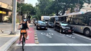 Ao lado de uma pista repleta de carros e ônibus, mulher para sua bicicleta na ciclovia construída ao lado da via para automotores