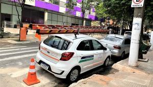 Carro branco com uma escada em cima estacionado em uma rua bem em frente a uma rampa, impossibilitando a saída de pessoas com mobilidade reduzida ou carrinhos de bebê