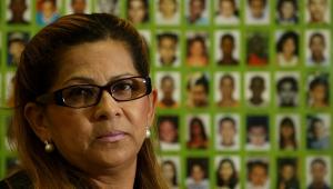 De óculos, Ivanise Esperidião da Silva Santos, presidente da ONG Mães da Sé, posa em frente a um cartaz com fotos de crianças desaparecidas