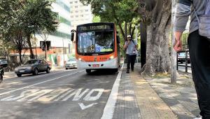Ônibus laranja, com a localização Pq. Dom Pedro II no letreiro, para no ponto de ônibus, pouco antes da palavra ônibus escrita para indicar o corredor; a via é arborizada, dois carros andam à direita do coletivo e um homem, de boné, mascara, camiseta e calça, anda pela calçada e espaço destinado aos ônibus é limitado