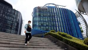 Homem desce uma escada em frente a um prédio comercial na China