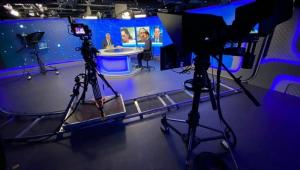 Foto do estúdio de Os Pingos nos Is mostra Vitor Brown e Augusto Nunes na bancada e, atrás deles, o telão com Ana Paula, Guilherme Fiuza e José Maria Trindade