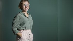 Mulher em frente a um fundo verde usando camisa verde, calça social rosa, sorrindo, com as mãos nos bolsos. Usa óculos de grau, tem cabelo loiro escuro curto e pele branca