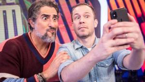 """Tiago Leifert seguro celular com as duas mãos e tira uma foto dele com Marcos Mion, ambos fazendo careta no estúdio de """"Caldeirão"""", na Globo"""