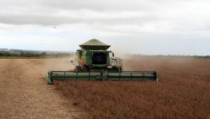 Com o céu nublado no horizonte, trator passa fazendo a colheita de soja em fazenda