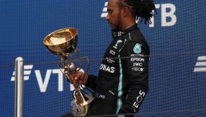 Com o joelho flexionado, vestindo o macacão preto da Mercedes, Lewis Hamilton segura o troféu do GP da Rússia com a mão esquerda