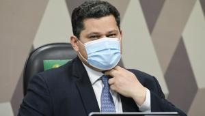 Sentado em frente a um notebook, vestido com trajes sociais e usando máscara, Davi Alcolumbre ajeita a gravata com a mão esquerda