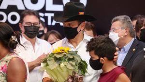De chapéu de cowboy e máscara, João Doria passa a mão na cabeça de menino e conversa com cidadãos de Barretos