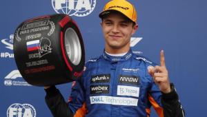 Com o macacão da McLaren e boné amarelo, o piloto Lando Norris segura um pneu com a mão direita e faz o número 1 com a esquerda